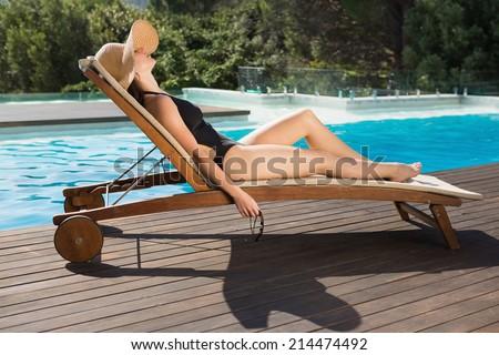 Side view of beautiful young woman in bikini relaxing by swimming pool - stock photo