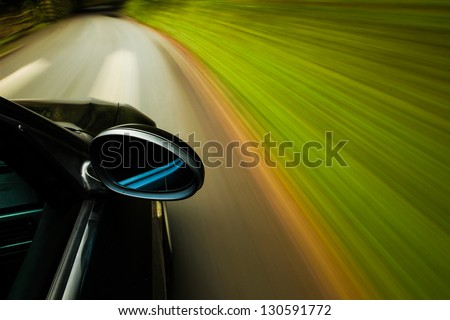Side view of black car driving on forest road. - stock photo