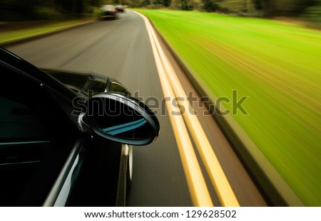 Side view of black car driving on the country road. - stock photo