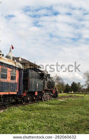 Side view of black old train wagon, in cloudy sky.