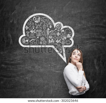 Side view of business lady, student, who is thinking about new business concepts. Drawn cloud with business icons on the black chalkboard. - stock photo