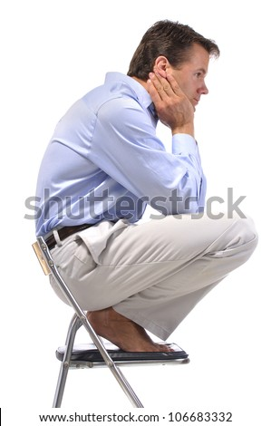 Side view of business man squatting barefoot on office chair with white background