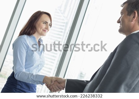 Side view of business people shaking hands in office - stock photo
