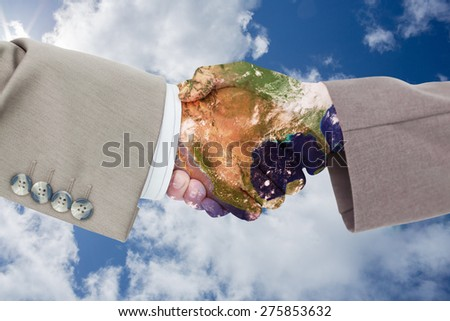 Side view of business peoples hands shaking against bright blue sky with clouds - stock photo