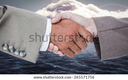 Side view of business peoples hands shaking against calm sea with lighthouse - stock photo