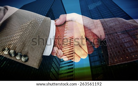 Side view of business peoples hands shaking against low angle view of skyscrapers - stock photo
