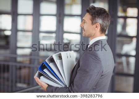 Side view of businessman carrying files stack in office - stock photo