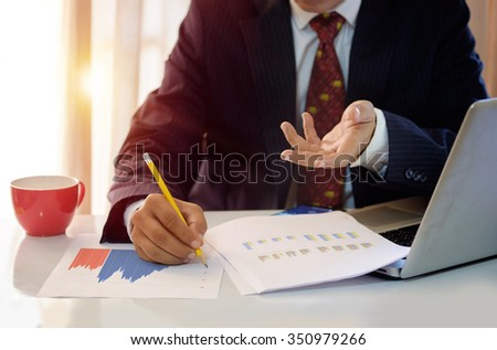 side view of businessman discussing charts on the paper reported in office. - stock photo