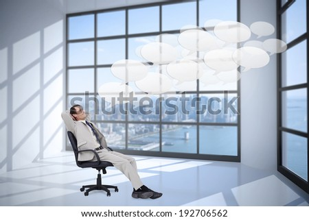 Side view of businessman leaning back in his chair against room with large window showing city