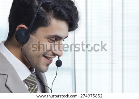 Side view of businessman wearing headset in office