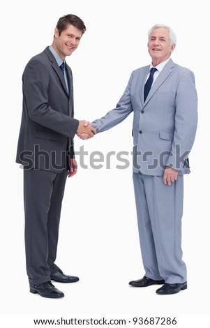 Side view of businessmen shaking hands against a white background - stock photo