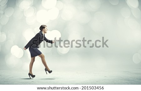 Side view of businesswoman in suit ready to run