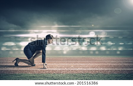 Side view of businesswoman in suit ready to run - stock photo