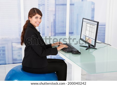 Side view of businesswoman using computer while sitting on fitness ball at desk in office - stock photo