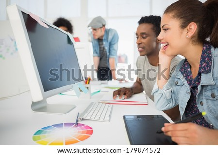 Side view of casual photo editors using graphics tablet in the office - stock photo