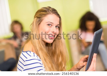 Side view of casual young woman using digital tablet in office - stock photo