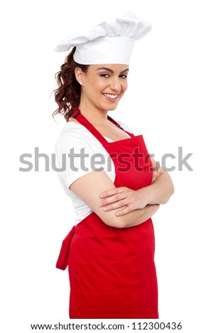 Side view of cheerful chef posing casually with her arms crossed - stock photo
