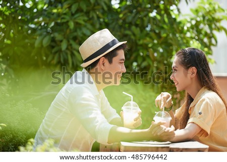 Side view of cheerful Vietnamese couple enjoying milkshakes in outdoor cafe