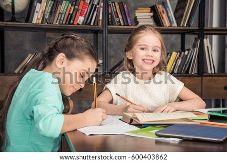 side view of classmates doing homework together in library