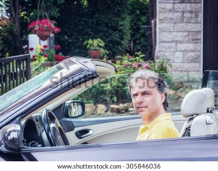 Side view of classy  40 years old sportsman with three-day beard and salt and pepper hair wearing a yellow polo shirt while he is driving a dark brown car in residential neighborhood