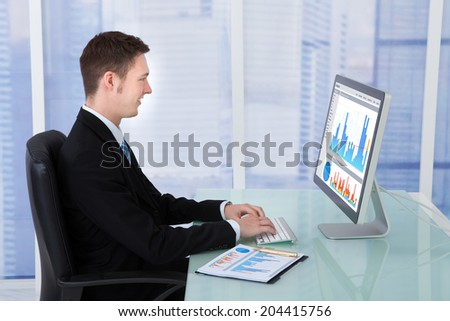 Side view of concentrated businessman working on computer at desk in office - stock photo