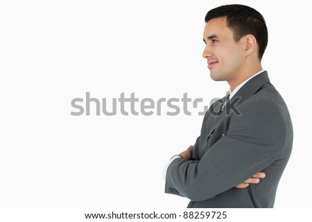 Side view of confident businessman with arms folded against white background