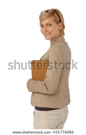 Side view of confident smiling businesswoman looking left, holding folder. - stock photo
