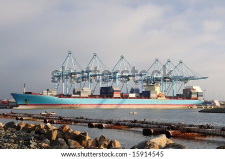 Side view of container ship being loaded and unloaded with cargo in the Port of Long Beach, California