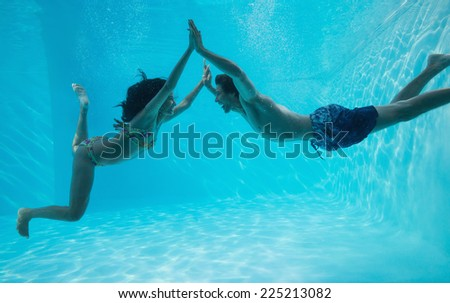 Side view of couple holding hands and swimming underwater in the swimming pool - stock photo