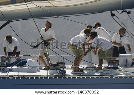 Side view of crew members working on sailboat - stock photo