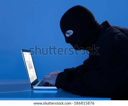 Side view of criminal using laptop to hack data at table - stock photo