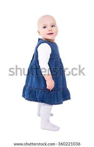 side view of cute baby girl standing isolated on white background - stock photo