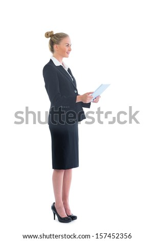 Side view of cute blonde businesswoman working with her tablet on white background - stock photo