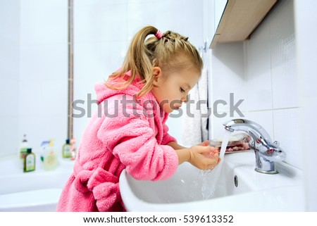 Side view of cute little girl with ponytail in pink bathrobe washing her hands. Copyspace