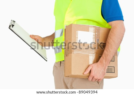 Side view of delivery man with delivery note and parcel against a white background - stock photo