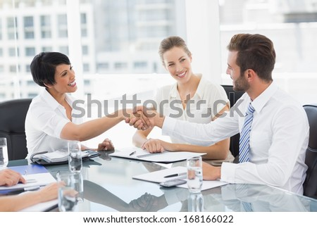 Side view of executives shaking hands after a business meeting in the office - stock photo