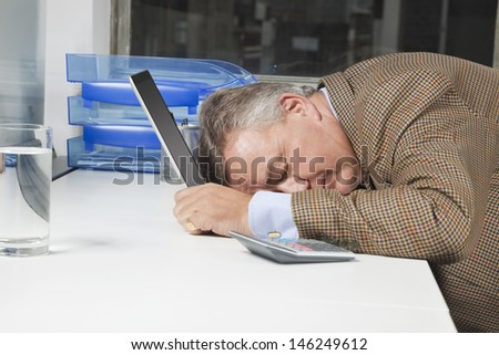 Side view of exhausted businessman with head on laptop in office - stock photo