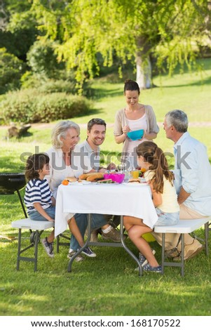 Side view of extended family dining at outdoor table - stock photo