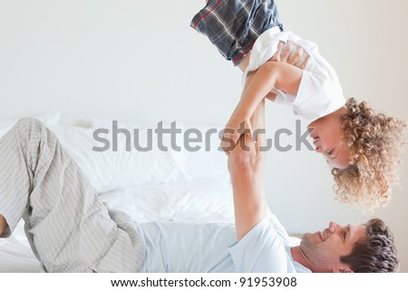 Side view of father lifting smiling child on bed - stock photo