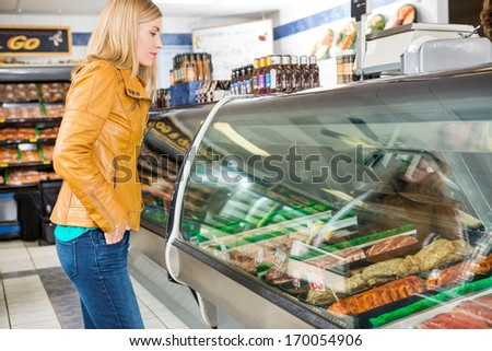 Side view of female customer selecting meat at butcher's shop - stock photo