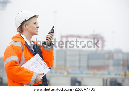 Side view of female engineer using walkie-talkie in shipping yard - stock photo