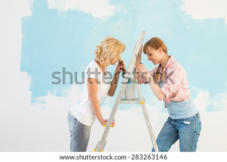 Side view of female friends painting together in new home - stock photo
