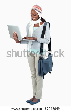 Side view of female student with laptop and winter clothing against a white background - stock photo