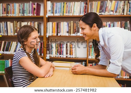 Side view of female teacher and little girl in the library