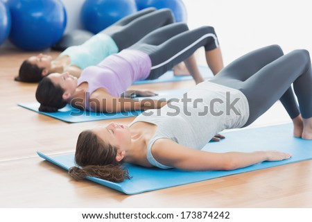 Side view of fit class exercising in row at fitness studio - stock photo