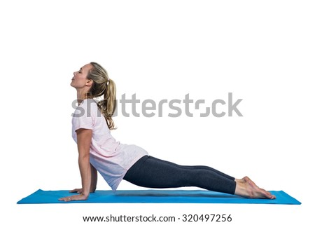 Side view of fit woman exercising on mat against white background