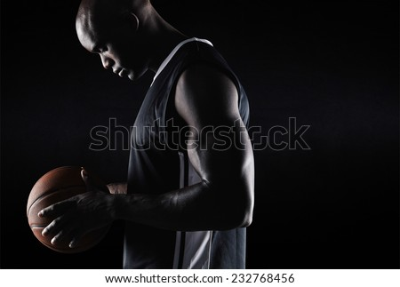 Side view of fit young basketball player holding ball against black background with copy space. African american basketball player with ball. - stock photo