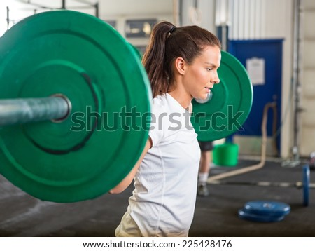 Side view of fit young woman lifting barbell in cross training box - stock photo
