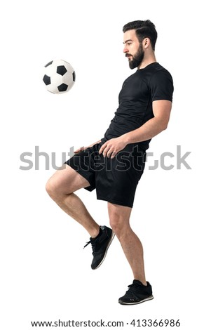 Side view of football or futsal player juggling ball with his knee. Full body length portrait isolated over white background.  - stock photo