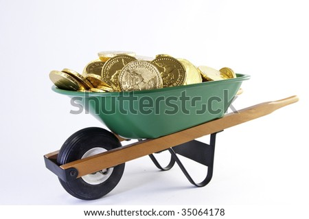 Side view of gold coins in a green wheel barrel.It is on a white background. - stock photo